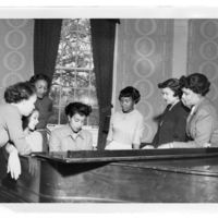 Students Gather Around a Piano in Bumstead Hall