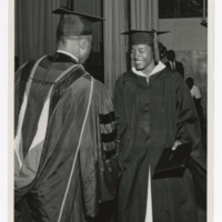 A Graduate Shakes Hands With James P. Brawley on stage at Commencement