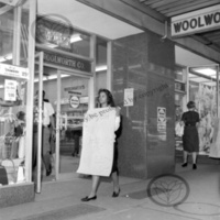 Woman walking picket line in front of Woolworth's<br />