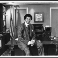 Maynard Jackson sitting on desk in Mayor's office